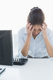 Businesswoman suffering from headache in front of computer Stock Photos