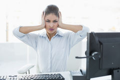 Businesswoman suffering from headache in front of computer Royalty Free Stock Photo