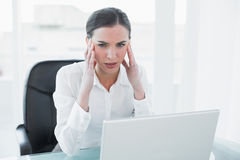 Businesswoman suffering from headache in front of laptop Royalty Free Stock Photography