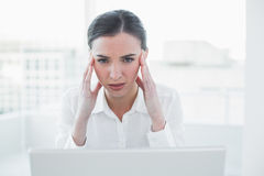 Businesswoman suffering from headache in front of laptop Royalty Free Stock Photos