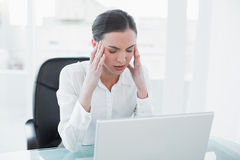 Businesswoman suffering from headache in front of laptop Stock Photography