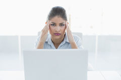 Businesswoman suffering from headache with laptop at office Royalty Free Stock Image