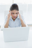 Businesswoman suffering from headache with laptop at office Stock Photo