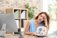 Businesswoman suffering from heat in front of small fan. At workplace royalty free stock image