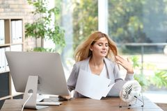 Businesswoman suffering from heat in front of small fan. At workplace stock photos