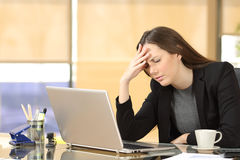 Businesswoman suffering migraines at work royalty free stock photography