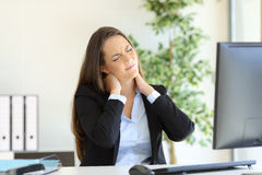 Businesswoman suffering neck pain. Sitting in a chair while working with a desktop computer in her workplace at office royalty free stock photography