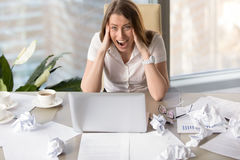 Businesswoman suffering from nervous breakdown. Stressful young businesswoman shouting at desk with laptop. Female entrepreneur suffers from nervous breakdown royalty free stock photos