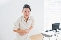 Businesswoman suffering from stomach pain in office Royalty Free Stock Image
