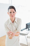 Businesswoman suffering from wrist pain in office Royalty Free Stock Photos