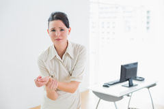 Businesswoman suffering from wrist pain in office Royalty Free Stock Photo