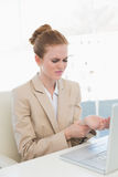 Businesswoman suffering from wrist pain in office Stock Images