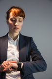 Businesswoman in suit checking the time Stock Images