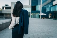 Businesswoman with suit in hand, back view. Business center on background. Modern financial building, cityscape. Successful female businessperson Royalty Free Stock Images