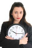 Businesswoman in suit holding a clock Stock Images