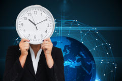 Businesswoman in suit holding a clock Stock Image
