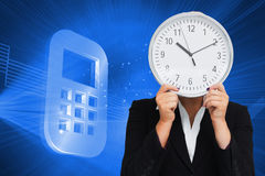 Businesswoman in suit holding a clock Stock Photos