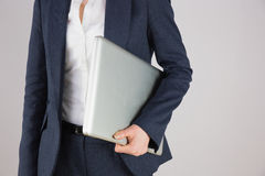 Businesswoman in suit holding laptop Royalty Free Stock Images