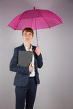 Businesswoman in suit holding pink umbrella and notepad Royalty Free Stock Photos