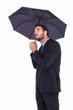 Businesswoman in suit holding umbrella while looking up Royalty Free Stock Photo