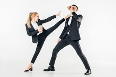 businesswoman in suit kicking businessman with coffee to go royalty free stock images