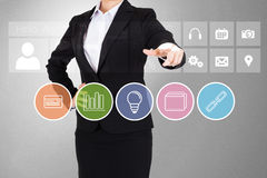 Businesswoman in suit pointing finger at business app buttons Royalty Free Stock Images