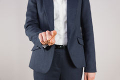 Businesswoman in suit pointing finger Stock Photography