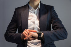 Businesswoman in suit pointing to watch Stock Image