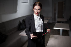 Businesswoman in suit and with red lips and with tablet;. Sexy serious woman with red glasses keeps tablet; strong business lady with mobile device; corporate Royalty Free Stock Photo