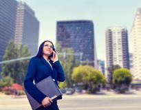 Businesswoman in suit talks by phone outdoor. Businesswoman in suit talks by mobile phone outdoor, business center on background. Successful female Royalty Free Stock Photography