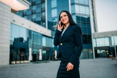 Businesswoman in suit talks by phone outdoor. Businesswoman in suit talks by mobile phone outdoor, business center on background. Modern financial building Royalty Free Stock Images