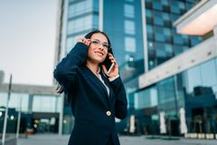 Businesswoman in suit talks by phone outdoor. Businesswoman in suit talks by mobile phone outdoor, business center on background. Successful female Royalty Free Stock Photo