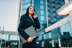 Businesswoman in suit talks by phone outdoor. Businesswoman in suit talks by mobile phone outdoor, business center on background. Modern financial building Stock Images