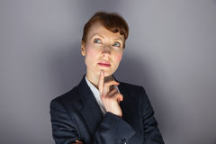 Businesswoman in suit thinking with finger on chin Stock Photos
