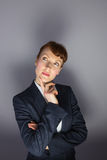Businesswoman in suit thinking with finger on chin Stock Photo