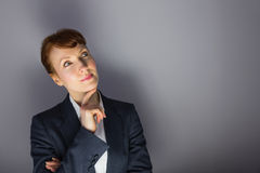 Businesswoman in suit thinking with finger on chin Royalty Free Stock Image