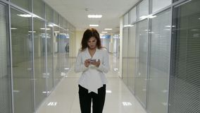 Businesswoman in suit walking and mobile phone in her hands in corridor of office stock footage