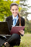 Businesswoman in suit working on grass Stock Photo