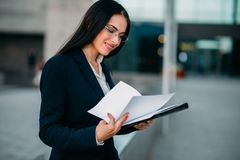 Businesswoman in suit works, business center. Businesswoman in suit works with notebook outdoor, business center on background. Modern financial building Royalty Free Stock Photography