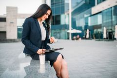 Businesswoman in suit works on laptop outdoor. Modern building, financial center, cityscape. Female businessperson working Stock Image