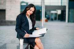 Businesswoman in suit works with notebook outdoor. Modern building, financial center, cityscape. Female businessperson working Stock Photography