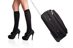 Businesswoman and suitcase. Businesswoman s legs in high stockings and high heels, holding a black suitcase Stock Photos