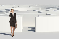 Businesswoman with suitcase going out labyrinth Royalty Free Stock Photo