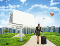 Businesswoman with suitcase on the road Royalty Free Stock Images