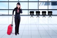 Businesswoman with suitcase and smartphone Stock Photography