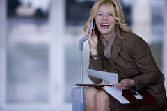Businesswoman with suitcase talking on cell phone Royalty Free Stock Photos