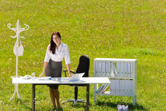 Businesswoman in sunny meadow nature office smile Stock Photos