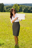 Businesswoman sunny meadow point at empty banner Stock Images