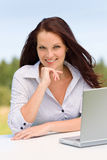 Businesswoman in sunny nature with laptop smile Stock Photo