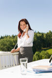 Businesswoman in sunny nature office calling. Young businesswoman in sunny nature office calling standing behind table stock image